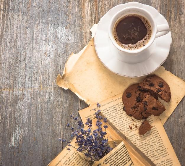 Xícara de café expresso com livro na mesa.