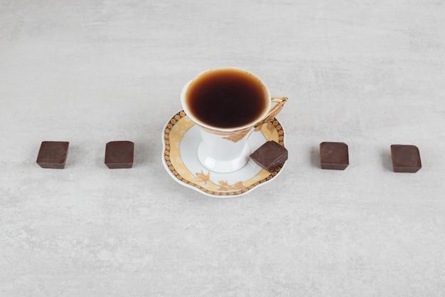 Xícara de café expresso com pedaços de chocolate na superfície de mármore