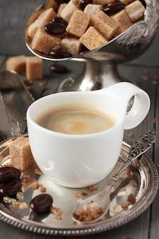 Xícara de café expresso, cubos de açúcar e doces de chocolate no fundo de madeira rústico