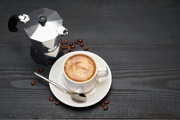 Xícara de café expresso e cafeteira mocha na mesa de madeira escura