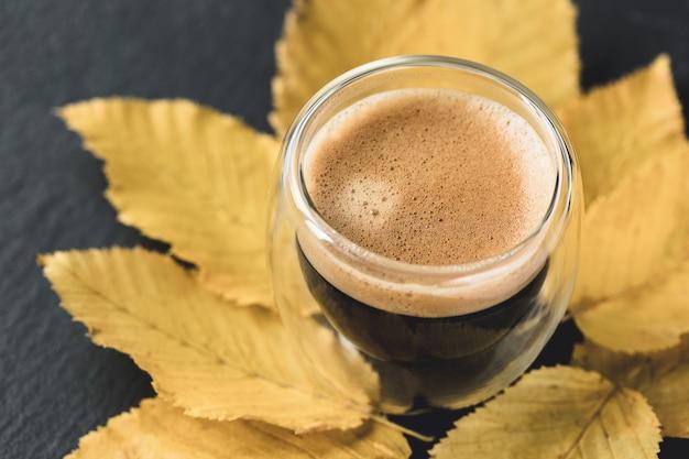 Xícara de café expresso e folhas amarelas de outono