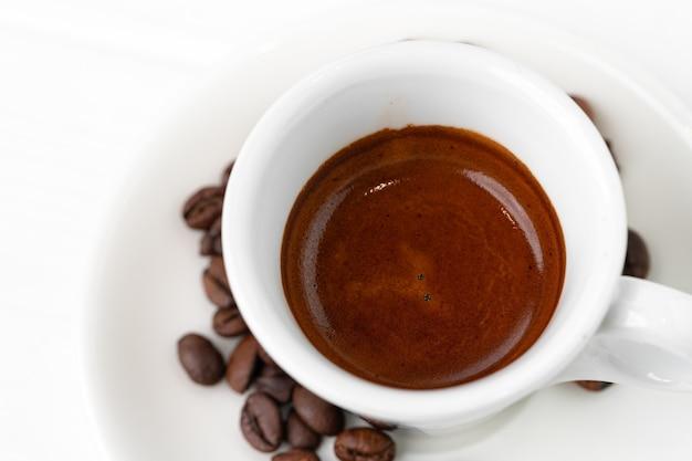 Xícara de café expresso e grãos de café na superfície branca close-up