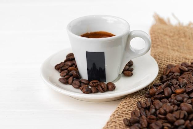 Xícara de café expresso e grãos de café na superfície branca