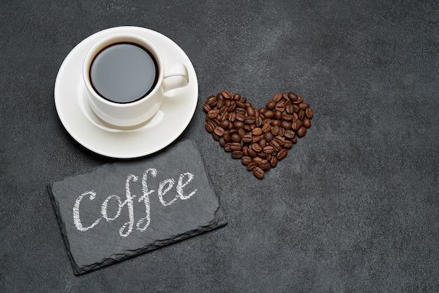 Xícara de café expresso e grãos de café torrados em forma de coração na mesa de concreto escuro