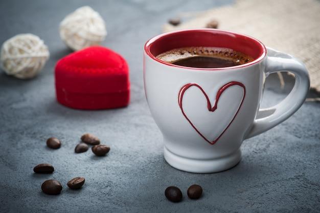 Xícara de café expresso, feijão, coração vermelho