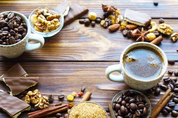 Xícara de café expresso preto em madeira natural com lanches saudáveis nozes e passas. copyspace no meio.