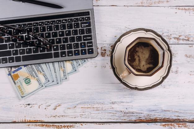 Xícara de café expresso preto no teclado do computador e dinheiro dólar americano na mesa de madeira mesa de trabalho