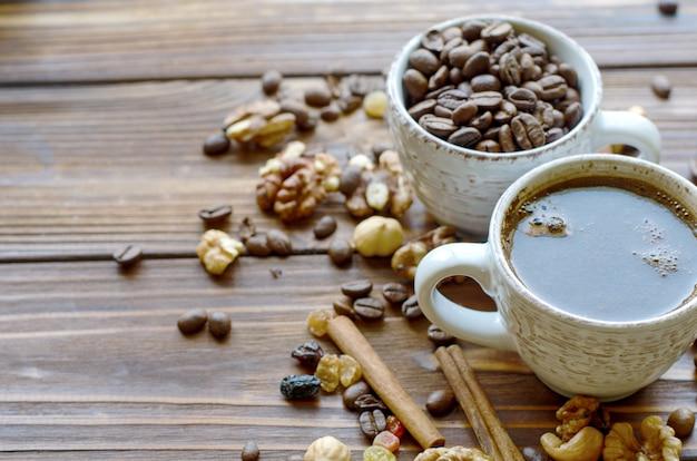 Xícara de café expresso preto sobre fundo de madeira natural com lanches saudáveis - nozes e passas