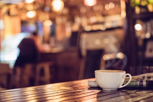 Xícara de café expresso quente com jornal na mesa de madeira iluminação bokeh desfocar o fundo