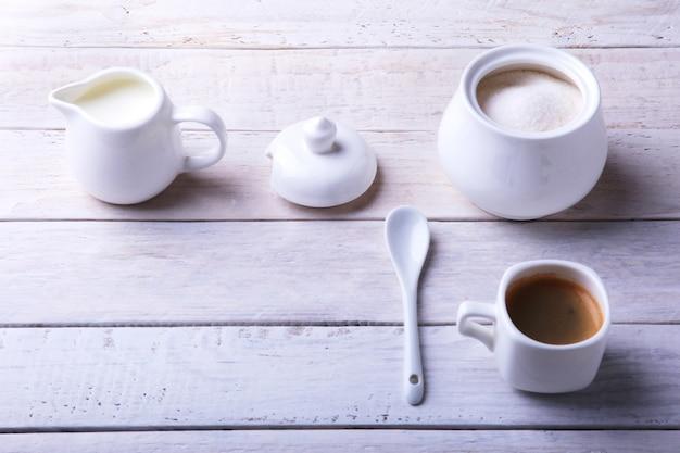 Xícara de café expresso quente, grãos de café, jarro de leite e tigela com açúcar no fundo branco