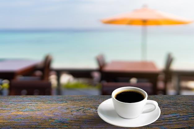 Xícara de café expresso quente no balcão de madeira com restaurante blur no verão à beira-mar