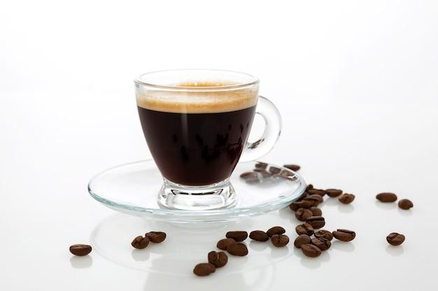 Xícara de café expresso transparente com grãos polvilhados na mesa. fundo branco.