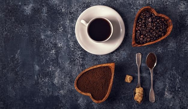 Xícara de café, feijão e pó moído na mesa de pedra.