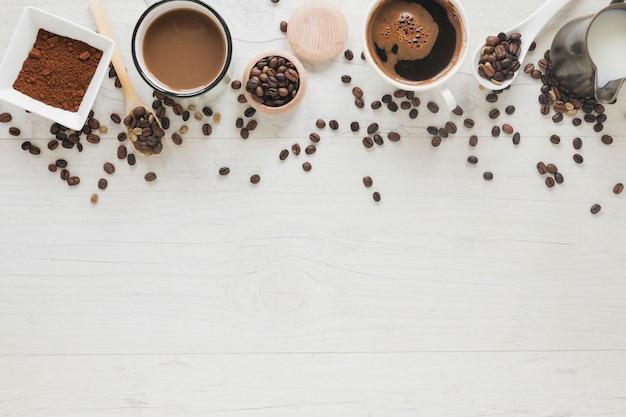 Xícara de café; feijão torrado; feijão cru; café em pó e leite na mesa de madeira branca