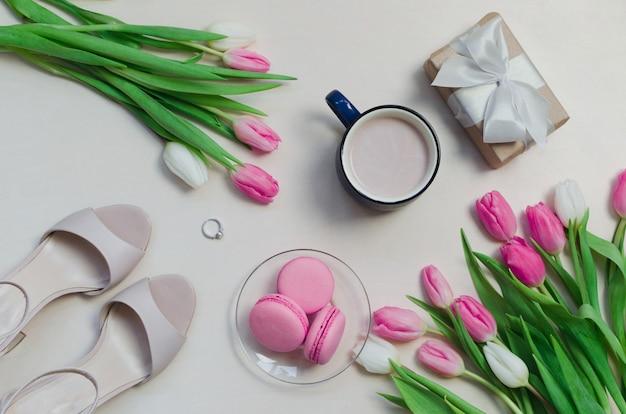 Xícara de café, flores de tulipa primavera e macarons rosa na vista superior de mesa pastel.