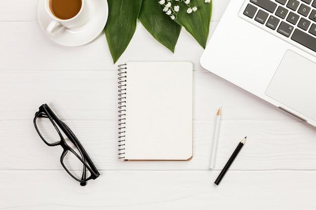 Xícara de café, folhas, bloco de notas em espiral, óculos na mesa de madeira de escritório