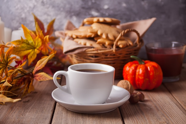 Xícara de café, folhas de outono, biscoitos, abóbora na mesa de madeira