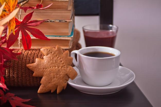 Xícara de café, folhas de outono, biscoitos. livros antigos de madeira cadeira preta. colheita de outono. conceito de outono.