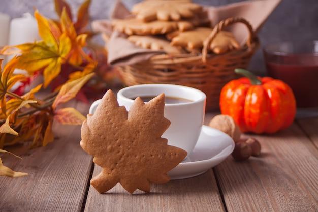 Xícara de café, folhas de outono, biscoitos na mesa de madeira. colheita de outono. conceito de outono.