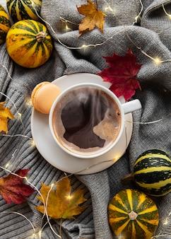 Xícara de café, folhas secas e lenço em uma mesa. camada plana, vista superior, espaço de cópia