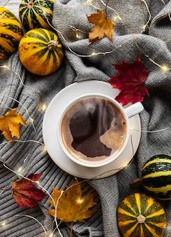 Xícara de café, folhas secas e lenço em uma mesa.