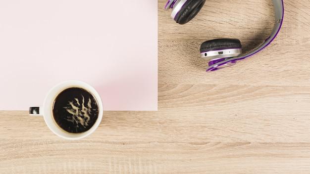 Xícara de café; fone de ouvido e papel em branco sobre fundo de madeira
