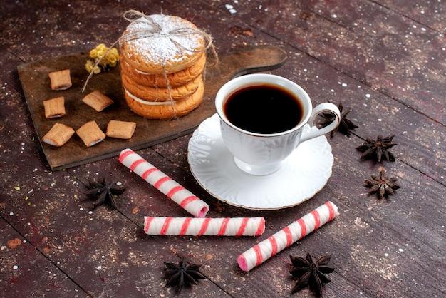Xícara de café forte e quente junto com biscoitos e bolo de biscoitos em uma mesa de madeira marrom, bolo de frutas assado