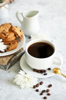 Xícara de café forte preto com grãos de café e biscoitos