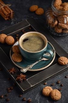 Xícara de café fresco com biscoitos amaretti em fundo escuro.