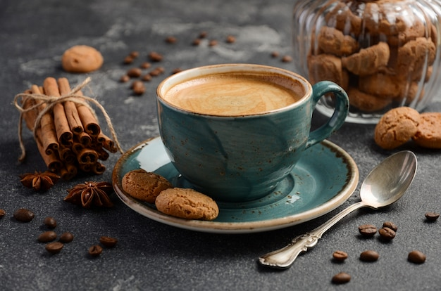 Xícara de café fresco com biscoitos amaretti em fundo escuro