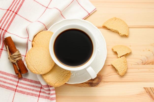 Xícara de café fresco com biscoitos de manteiga e paus de canela na toalha