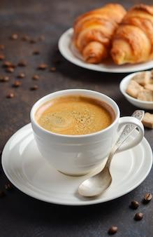 Xícara de café fresco com croissants em fundo escuro