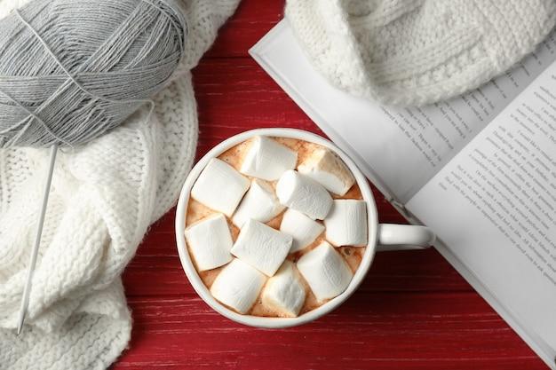Xícara de café fresco com marshmallow e manta de malha em fundo de madeira, vista superior