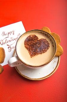 Xícara de café fresco da manhã com cartão de dia dos namorados e biscoitos de coração, no espaço da cópia de mesa vermelha.