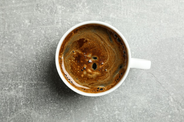 Xícara de café fresco na mesa cinza, vista superior