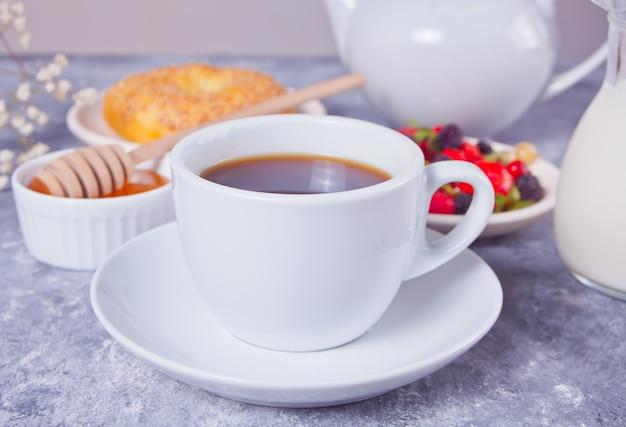 Xícara de café, frutas, pão e mel no café da manhã.