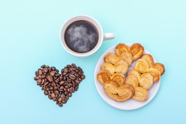 Xícara de café fumegante, massa folhada e grãos de café em forma de coração em uma vista superior da superfície azul