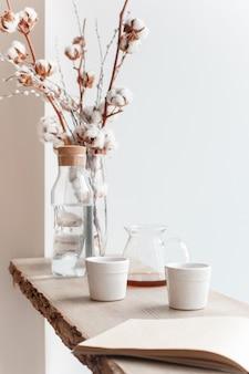 Xícara de café, galho de árvore, peitoril da janela de madeira