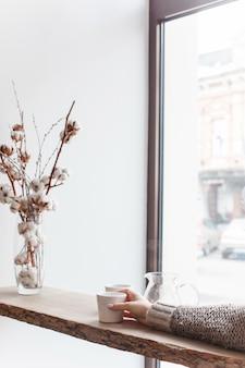Xícara de café, galho de árvore, peitoril de janela de madeira