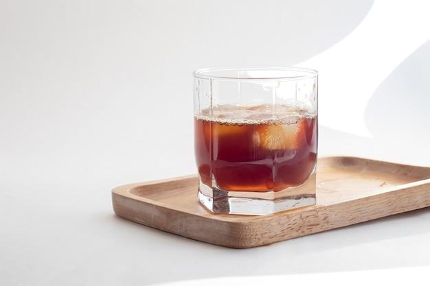 Xícara de café gelado com cubos de gelo em uma placa de madeira de bambu