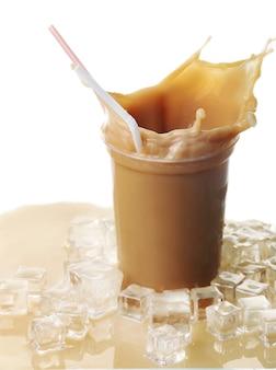 Xícara de café gelado com respingos na mesa