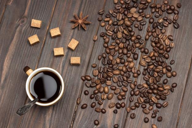 Xícara de café. grãos de café anis estrelado e pedaços de açúcar mascavo na mesa.