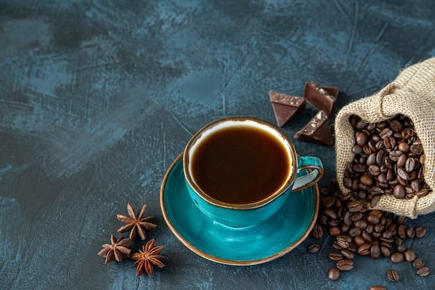 Xícara de café, grãos de café, chocolate e anis estrelado em um fundo de mesa escuro
