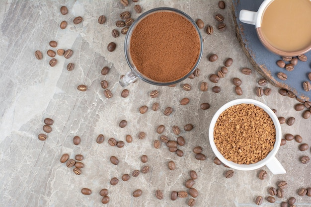 Xícara de café, grãos de café e café moído na superfície de mármore.