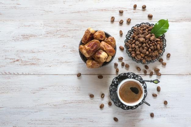 Xícara de café, grãos de café e datas frescas na mesa de madeira branca.