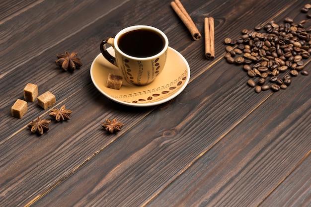 Xícara de café. grãos de café espalhados na mesa, anis estrelado e pedaços de açúcar mascavo
