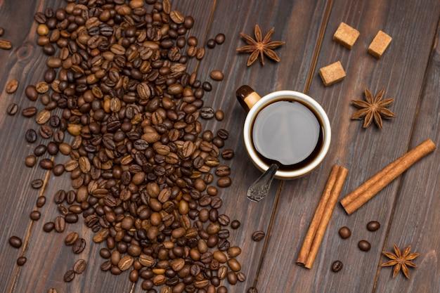 Xícara de café. grãos de café espalhados na mesa, anis estrelado, paus de canela e pedaços de açúcar mascavo.