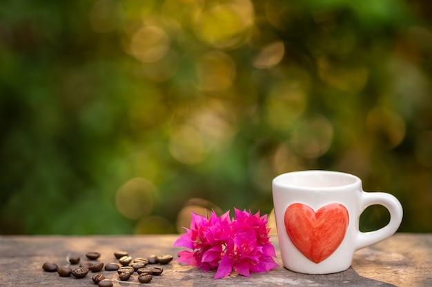 Xícara de café, grãos de café torrados e buganvílias flor na placa de madeira.