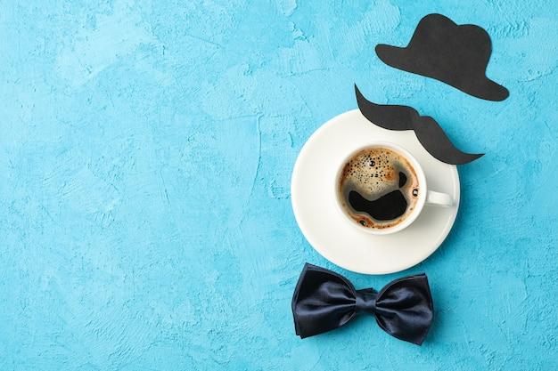 Xícara de café, gravata borboleta, bigode decorativo e chapéu sobre fundo azul, espaço para texto e vista superior