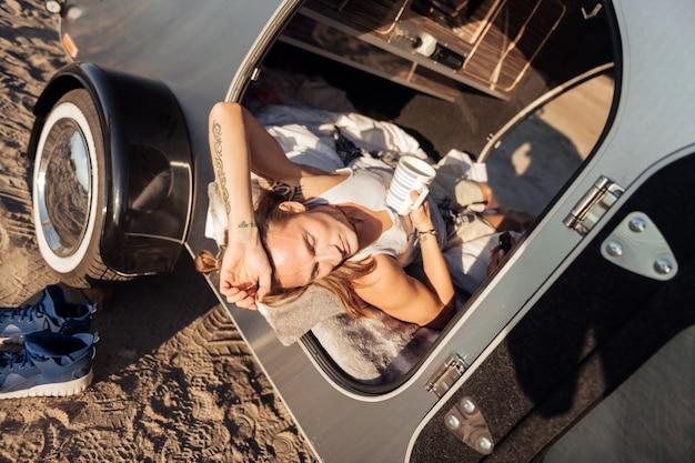 Xícara de café. homem bonito de cabelos loiros deitado em seu trailer compacto tomando uma xícara de café